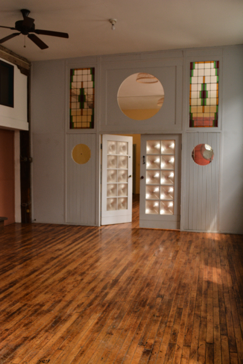 The center space in the loft showing stain glass and oversized double doors