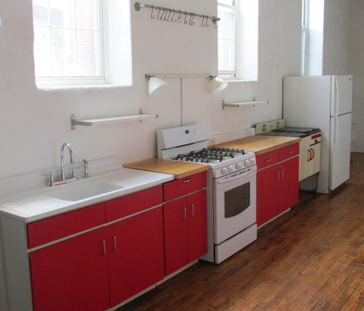Photograph showing the butcher block counters farm house sink and 5 burner stove with grill. in the loftss kitchen